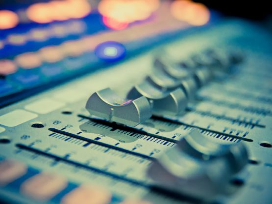 Close up on volume faders on an audio mixing desk
