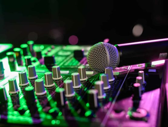 Live analog mixing console in Sydney with a wireless handheld microphone on top of it